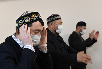 Muslim clerics take part in prayers during Eid al-Fitr, a Muslim festival marking the end the holy fasting month of Ramadan, at a mosque in Omsk