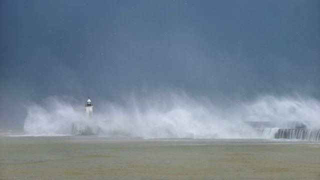 Massive waves crash over harbour wall onto lighthouse during huge storm on English coastline in Newhaven, amazing images showing power of the ocean