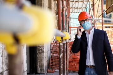 Ingegnere con casco arancione e mascherina Chirurgica lavora in un cantiere in città e parla con il cellulare