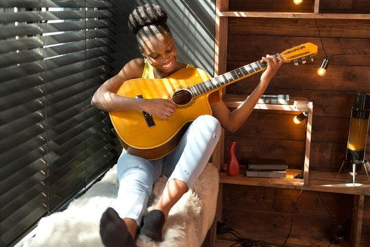 beautiful young african woman playing guitar