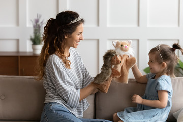 Happy young mother and little daughter wearing princess diadems, having fun with fluffy dolls, sitting on cozy couch, smiling mum and cute preschool girl playing doll theatre game at home