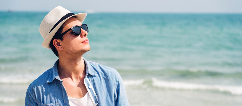 Portrait of smiling happy handsome man model enjoying and relax in fashionable sunglasses and hipster summer straw hat standing on the tropical beach and looking at camara.Summer vacations and travel