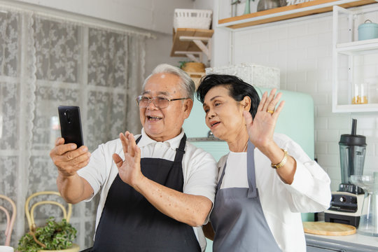 Portrait of an elderly Asian couple doing facetime video calling with a smartphone at home using the zoom app, online meetings, social media, new normal concepts