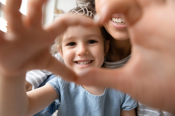 Keuken foto achterwand Texturen Close up little girl wearing princess diadem and mother showing heart sign with hands, looking through fingers at camera, taking selfie, happy mum and smiling daughter having fun together