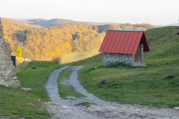 little hut with red roof and dirt road in beautiful forest landscape