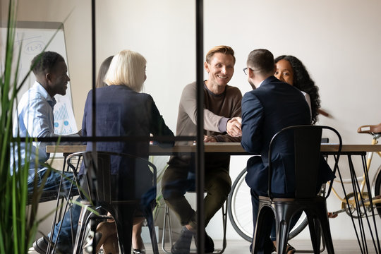 Smiling business partners shaking hands at meeting in boardroom with diverse employees team, making agreement, good legal deal, greeting or introduction, two businessmen handshaking at briefing