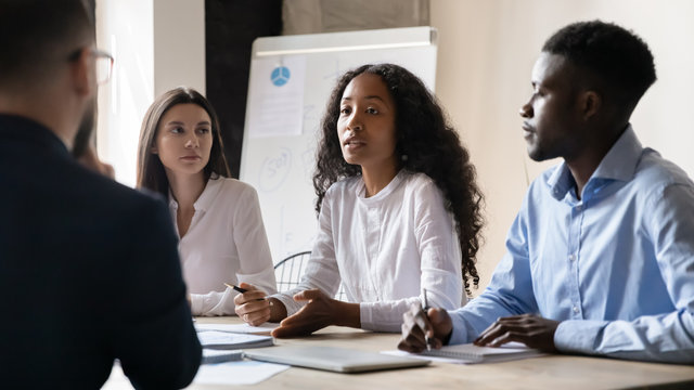 Confident African American businesswoman speaking at corporate meeting in boardroom, sharing startup ideas, serious female coach mentor training teaching staff, team leader giving instructions