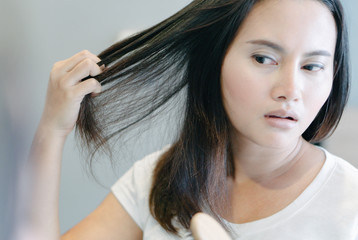 Fototapeta Close up woman hand holding hair loss problem for health care shampoo and beauty product concept