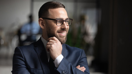 Obraz Smiling businessman wearing glasses dreaming about good future close up, touching chin, business vision concept, team leader standing in modern office, looking in distance, thinking about project - fototapety do salonu