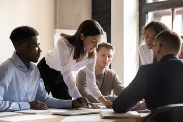 Diverse colleagues working on project together, sitting at table in boardroom, working with legal documents, financial report with statistics, employees engaged in teamwork at corporate meeting