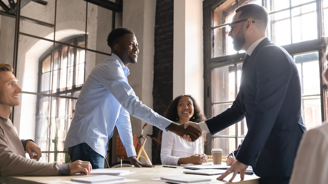 Happy diverse business partners handshaking at successful group negotiation, making agreement, good legal deal, signing contract, African American and Caucasian businessmen shaking hands at meeting