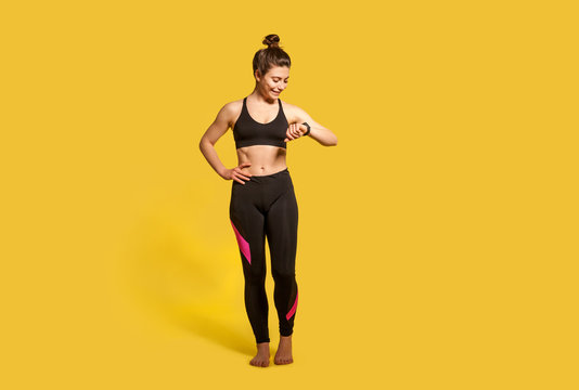 Happy athletic woman with hair bun in tight sportswear looking at wristwatch, checking pulse time on fitness tracker, smiling satisfied with health indicators after trainings. Sport activity, isolated