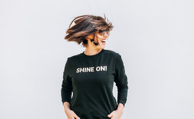 Wall Mural - Free feeling happy smiling woman posing in black sweatshirt with positive print Shine On. She rotating a head bacause a cheerful mood.