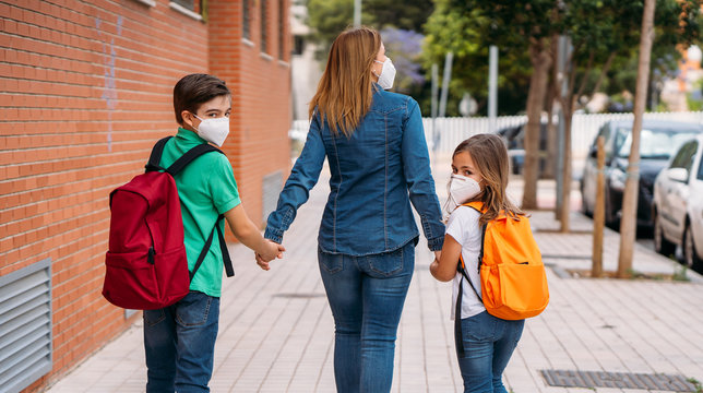 Mother with her children go to school with masks in coronavirus pandemic