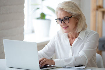 Focused middle-aged businesswoman in glasses sit at desk typing working on laptop, browse wireless internet, concentrated senior female employee consult client online using modern computer gadget