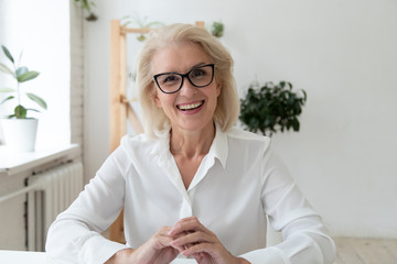 Headshot close up view of smiling middle-aged businesswoman in glasses have video call with...