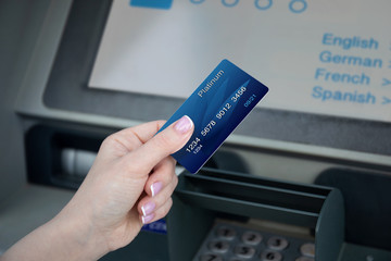 female hand holds credit card at ATM