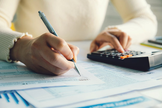 Closeup woman filling form of Individual Income Tax Return,