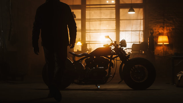 Custom Bobber Motorbike Standing in an Authentic Creative Workshop. Silhouette of a Rider Coming to a Bike. Vintage Style Motorcycle Under Warm Lamp Light in a Garage.