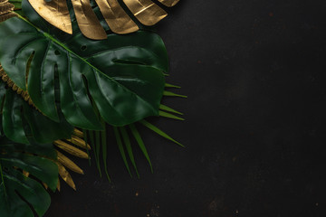 Creative layout with gold and green tropical palm leaves on black background. Minimal summer...