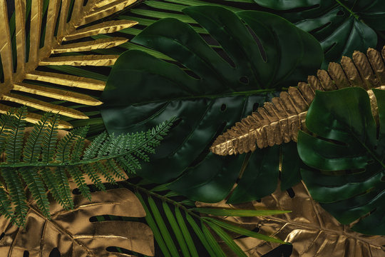 Creative layout with gold and green tropical palm leaves on black background. Minimal summer abstract pattern.