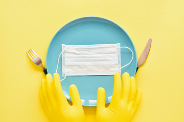empty plate, fork with knife, latex gloves and medical face mask - concept of the impact of the...