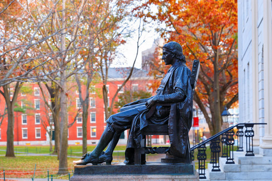 The Statue of John Harvard on campus of Harvard University at sunrise. Harvard University is a private Ivy League research university in Cambridge, MA.