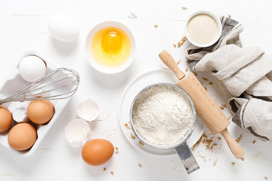 Baking homemade bread on white kitchen worktop with ingredients for cooking, culinary background, copy space, overhead view