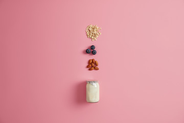 Variety of healthy ingredients for healthy breakfast. Yoghurt, oatmeal cereals, blueberry, almond nut to mix on pink background. Delicious products to prepare yummy nutrient porridge. Eating concept