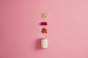 Organic nutrition, healthy breakfast concept. Yoghurt or vegan milk in jar, oatmeal cereals, raspberry and almond nut for making tasty snack. Natural ingredients. Vegetearian meal and dieting