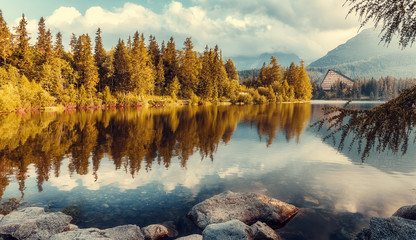 Fotomurales - Beautiful sunny landscape. View on mountain lake with crystal clear azure water in High Tatras. Slovakia. Red Boats on the water glowing in sunlight at sunset. Awesome Autumn landscape. Strbske pleso
