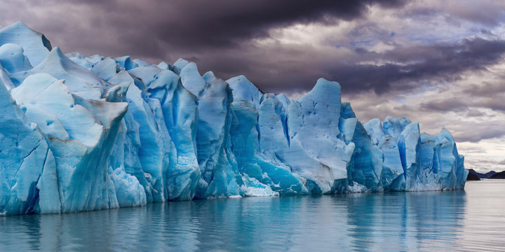 Scenic View Of Glacier By Sea Against Sky