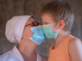 Family with child in mask on gray background. Mother in white coat and baby wear face mask during coronavirus and flu outbreak. .Mother puts her child face protective mask. Coronavirus quarantine