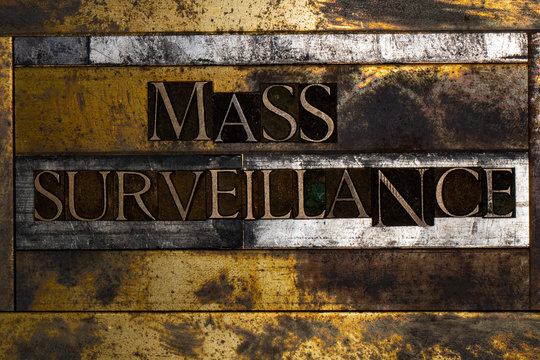 Photo of real authentic typeset letters forming Mass Surveillance text on vintage textured silver grunge copper and gold background