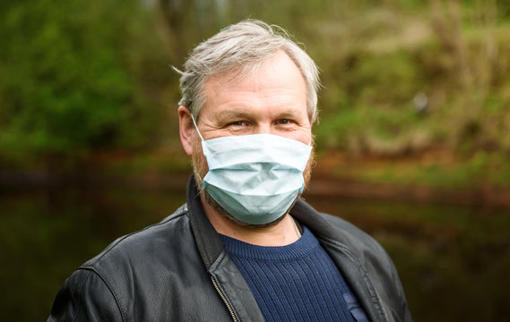 A happy man on a nature walk by the river in a medical mask rejoices at the end of the quarantine.