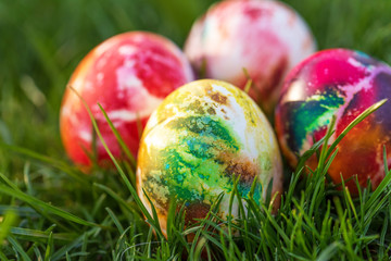 Traditionally painted Easter eggs hidden in grass.