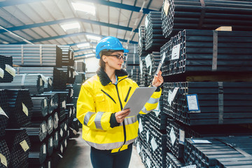 Woman worker checking the inventory in a steel warehouse