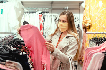 Woman shopping in fashion store wearing face mask