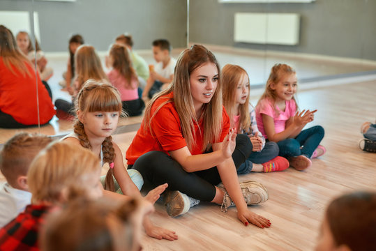 Dance class. Full length portrait of a postive young dance teacher talking to group of little happy girls and boys sitting on the floor in the dance studio