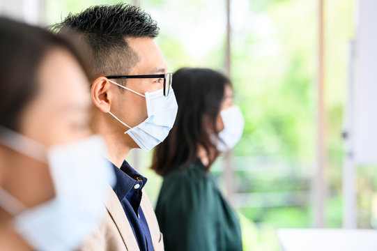 Row of Asian people wear protective face masks for safety and keep social distancing for new normal lifestyle for working in office