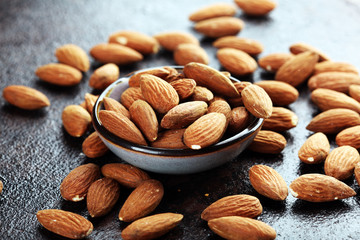 Almonds on a rustic background and almond in bowl.