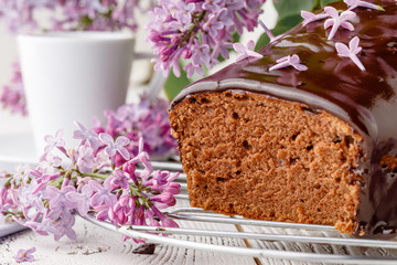 Brownie, watered with chocolate on a wooden background with a bouquet of lilacs