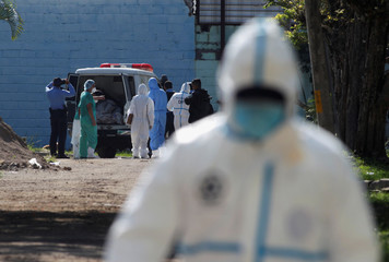 Forensic technicians work next to a car containing bodies after six inmates died and two more were injured in a violent brawl in the National Women's Penitentiary for Social Adaptation on the outskirts of Tegucigalpa
