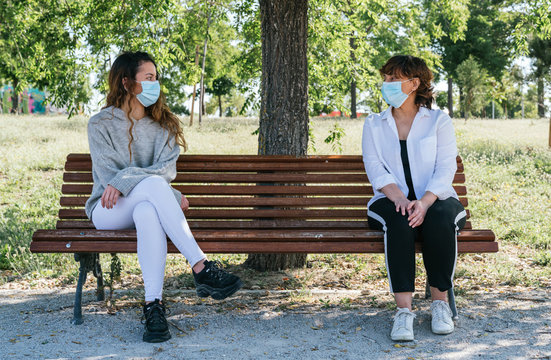 Social distance. Mother and daughter in social distance sitting on a park bench. Pandemic. Coronavirus. Maintaining safe distance sitting on a park bench. Safety distance.