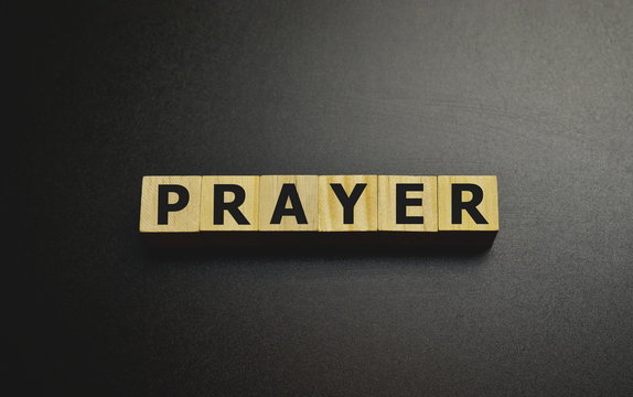 PRAYER word made with building blocks on gray.