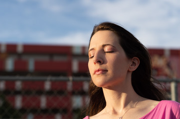 close up of Young woman in urban city with eye closed in the sunlight with pink makeup