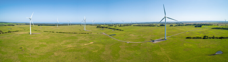 Wind farm and green grasslands in the summer - aerial panorama