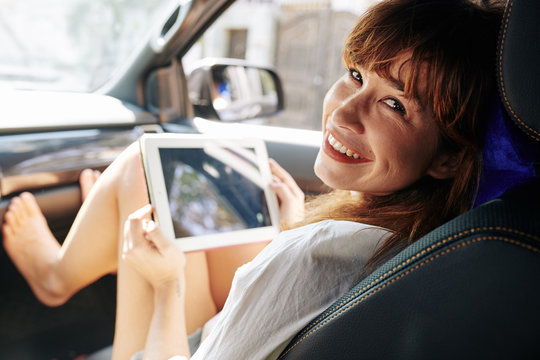 Barefoot young woman sitting on passenger seat with feet of dashboard, holding tablet computer and looking back at camera
