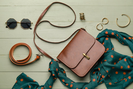 Stylish bag with female accessories on color wooden background