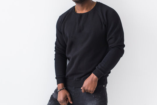 Street fashion concept - Close-up of African man wearing sweatshirt against white background.